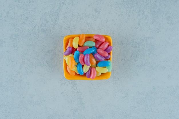 Een oranje bord met kleurrijke jelly bean-snoepjes op een witte ondergrond
