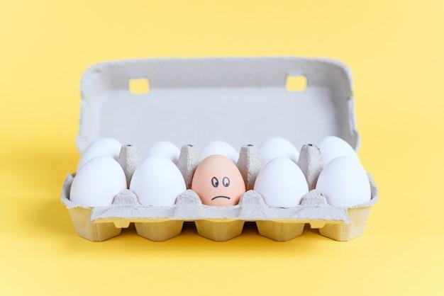 Een oranje ei met getekende droevig gezicht tussen witte eieren in een kartonnen bakje. anders dan andere.