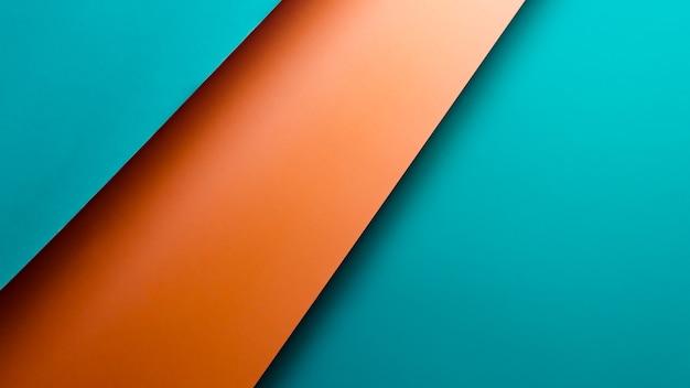 Een oranje en blauwe metalen plat lag achtergrond met scherpe lagen en schaduwen met kopie ruimte
