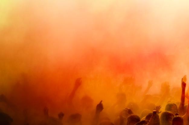 Een oranje holi kleurt over de menigte