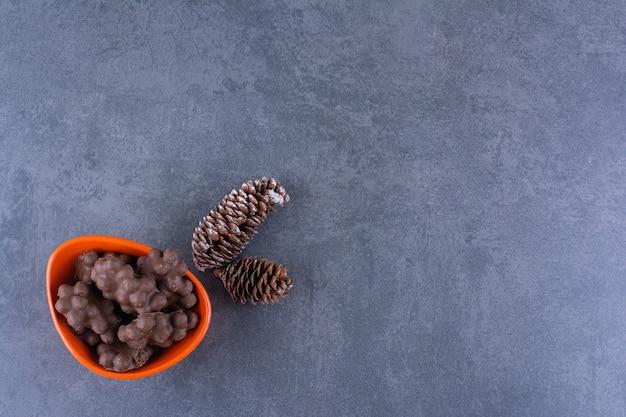 Een oranje kom melkchocolade met dennenappels op een steen.