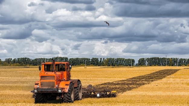 Een oranje moderne tractor ploegt het gouden aardeveld van tarwe