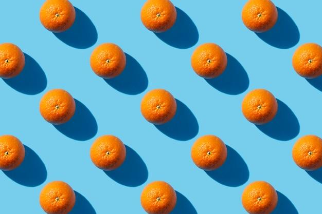 Een oranje op een blauwe achtergrond. hard licht. tropics concept, gezond eten, ontbijt, voeding, vakantie. plat lag, bovenaanzicht. patroon