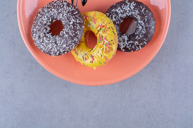 Een oranje plaat van heerlijke chocolade donuts met hagelslag.