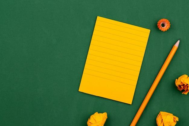 Een oranje vel papier ligt op een groen schoolbord dat een kader voor tekst vormt. in de buurt van potlood en verfrommelde pagina's. ruimte kopiëren plat leggen bovenaanzicht concept onderwijs.