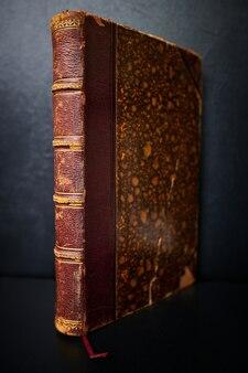 Een oud antiek boek staat op een donkere achtergrond
