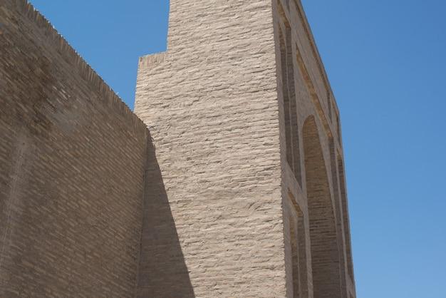 Een oud bakstenen gebouw met een toren. oude gebouwen van middeleeuws azië. buchara, oezbekistan