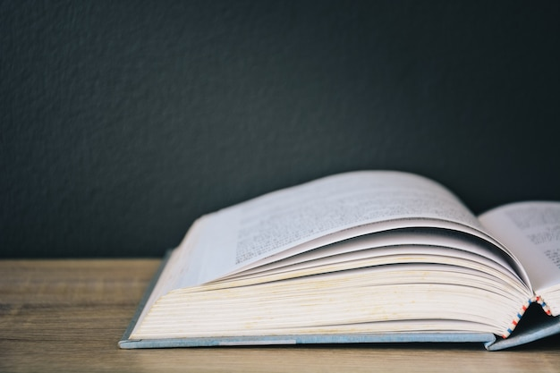 Een oud boek open op een houten tafel met een zwarte muurachtergrond en licht van bovenaf