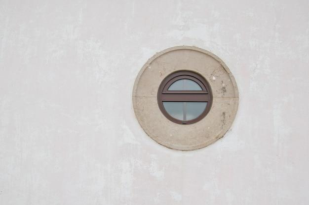 Een oud cirkelvenster op witte muur
