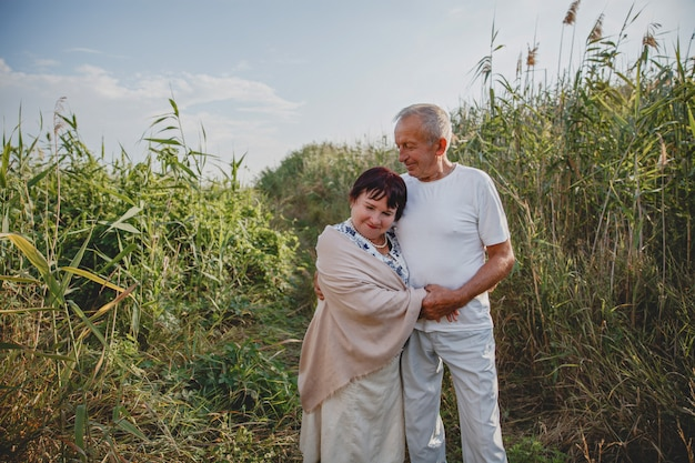 Een oud echtpaar op een zomerse wandeling in het veld