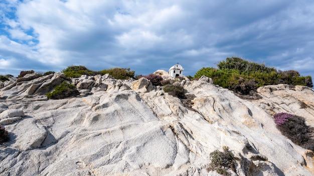 Een oud en klein heiligdom gelegen op rotsen nabij de egeïsche zeekust, struiken rondom, bewolkte hemel, griekenland