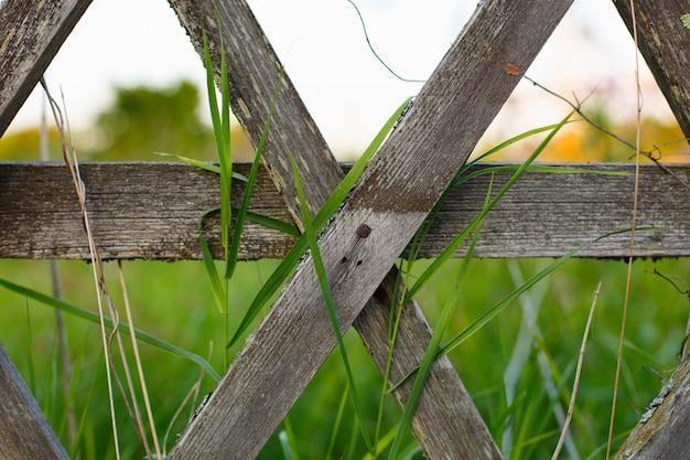 Een oud houten hek met een groen land veld erachter.