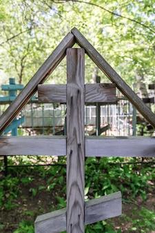 Een oud houten kruis staat op een verlaten graf op de begraafplaats verweerde houtstructuur en patroon
