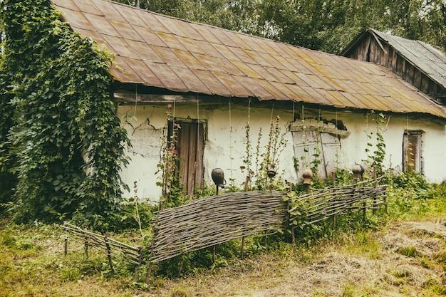 Een oud huis met een omheining in een arm dorp. vernietigd gebouw. zomer