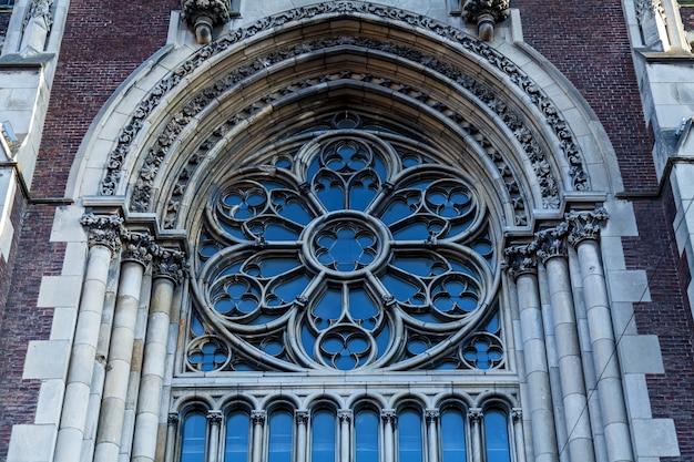 Een oud ijzeren raam met decoratieve elementen op de gevel van een kerk