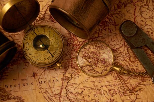 Een oud kompas met een gouden horloge en een beschamende trompet die op een papieren kaart liggen