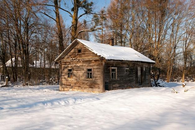 Een oud landelijk houten huis in de winter