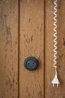 Een oud stopcontact en een stekker met een draad op een geschilderde houten huismuur
