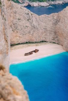 Een oud verroest schip, vernield, ligt aan de kust