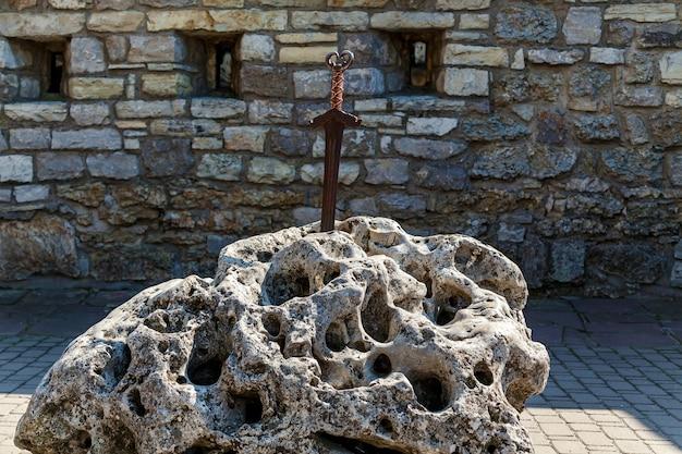 Een oud zwaard in een grote steen tegen een stenen muur met kleine ramen.