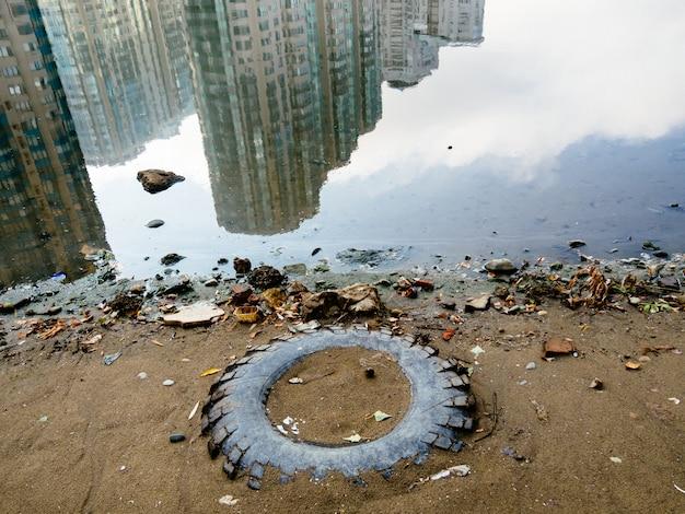 Een oude band van een wiel. vuilnis is verspreid aan de oever van het meer. reflectie van hoogbouw in het water