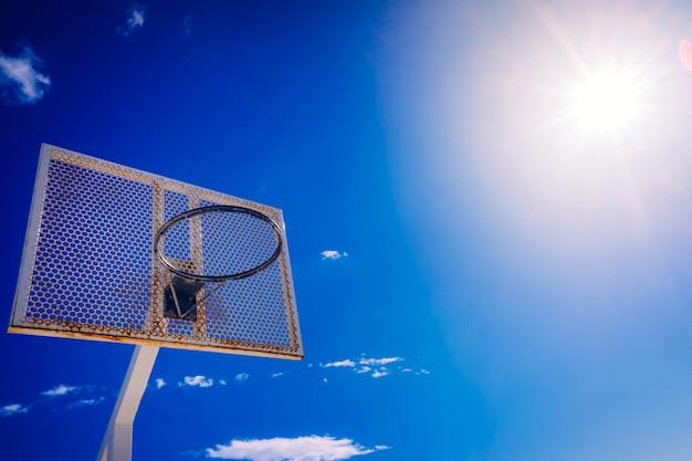 Een oude basketbalmand buiten een straat met blauwe hemel, exemplaarruimte voor tekst.