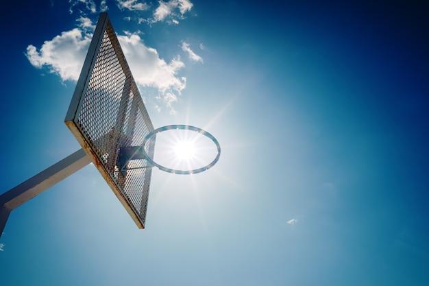 Een oude basketbalmand buiten een straat met blauwe hemel