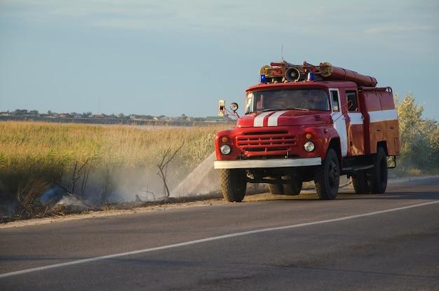 Een oude brandweerwagen blust een brand vlakbij de weg