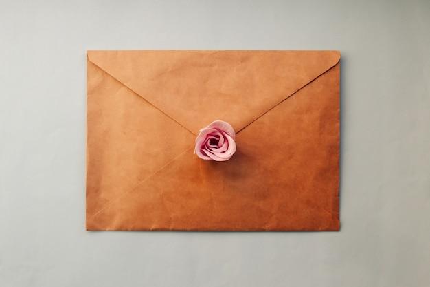 Een oude bruine envelop, roze nam bloem op een blauwe achtergrond toe. minimaal plat leggen