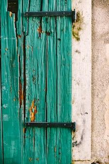 Een oude gebarsten groene loopdeur vastgemaakt aan een witte muur