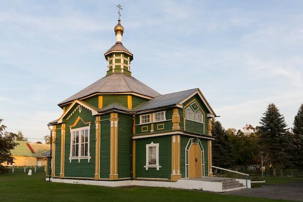 Een oude houten 19e-eeuwse kerk in groen met een gouden koepel en gouden kruis in warm zonlicht met een platform van groen gras