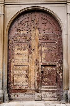 Een oude houten bruine deur met afbladderende verf in de ovale deur tussen de kolommen