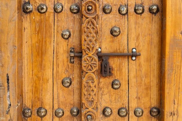 Een oude houten deur met metalen klink, gesloten, close-up, unaited arabische emiraten