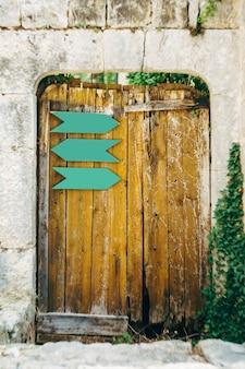 Een oude houten poort met metalen wijzers in de ovale opening van de stenen muur