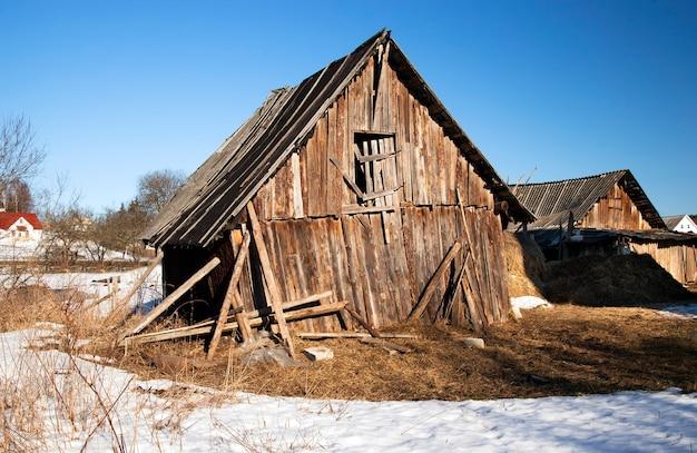 Een oude houten schuur die zijwaarts begon te vallen. wit-rusland