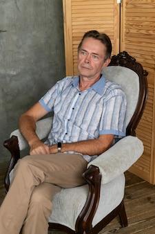 Een oude intelligente man rust op een leunstoel