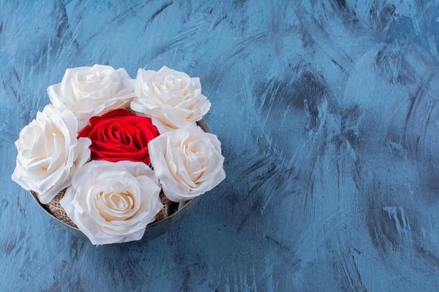 Een oude kom met witte en rode mooie verse rozen