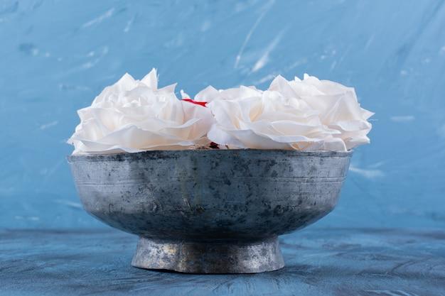 Een oude kom met witte mooie verse rozen.