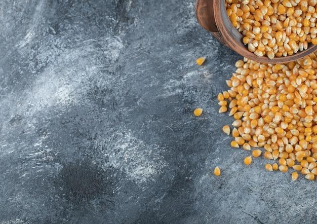 Een oude kom vol ongekookte popcornzaadjes.