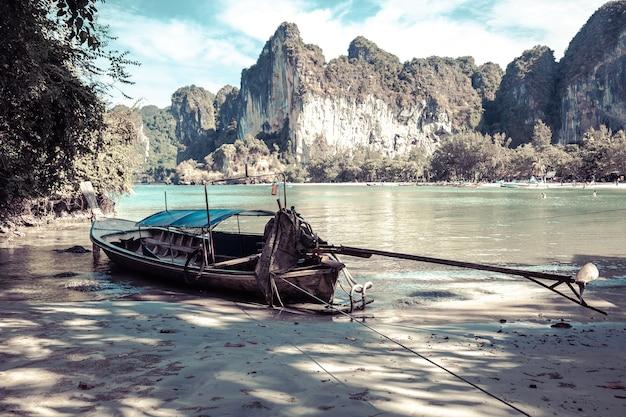 Een oude langstaartboot gemaakt van hout bij eb depressieve kleuren tropisch zandstrand