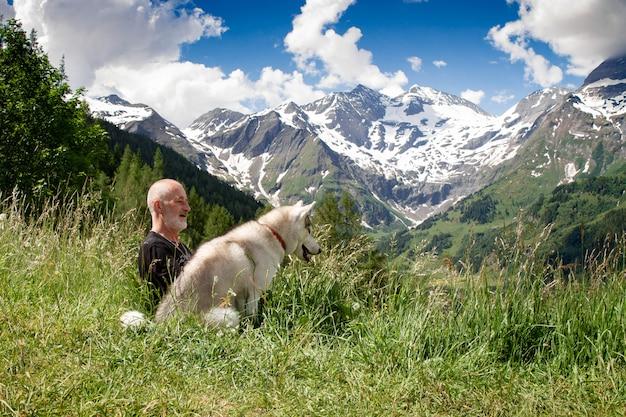 Een oude man en een sledehond lopen. actieve vrijetijdsgepensioneerde. loop met siberian husky.