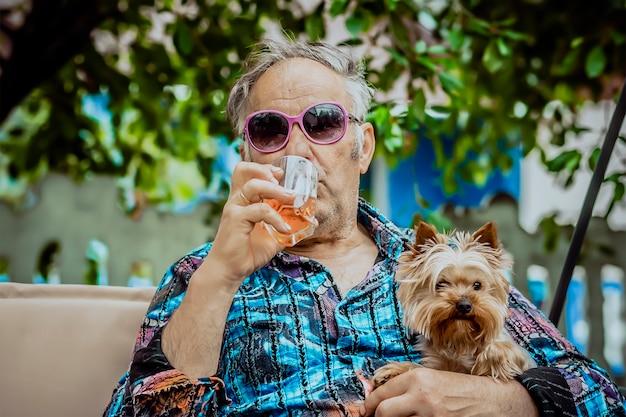 Een oude man met een hond die whisky drinkt