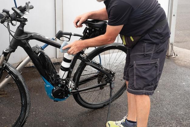 Een oude man wast zijn fiets en zorgt voor de details. servicestation. hogedrukpomp