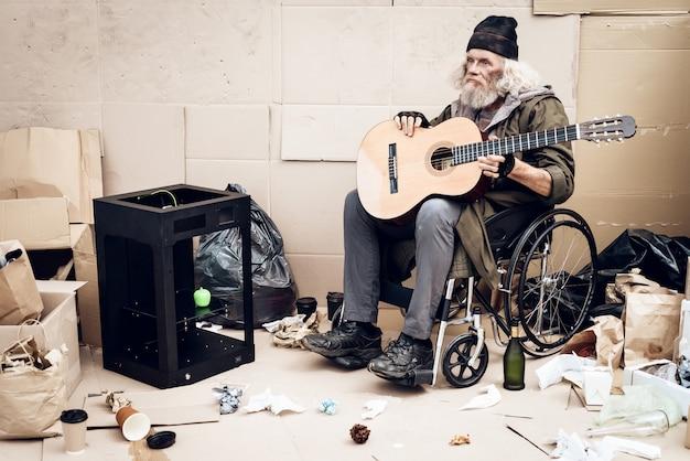 Een oude man zit in een rolstoel en speelt gitaar.