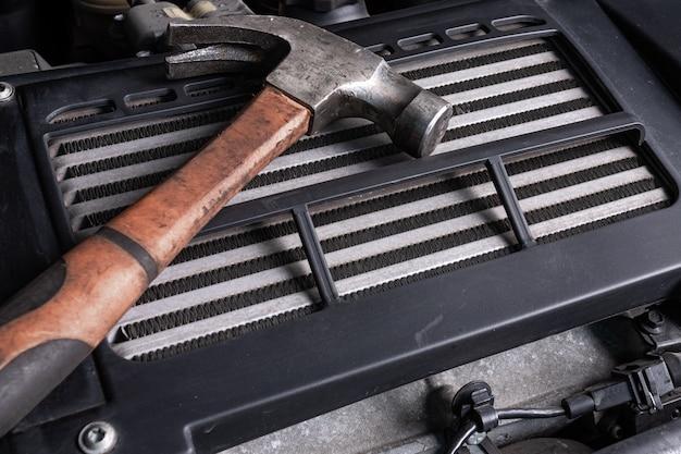 Een oude metalen hamer ligt onder de motorkap van een auto op een oliekoeler. concept autoreparatie en hulpmiddelen in de autodienst