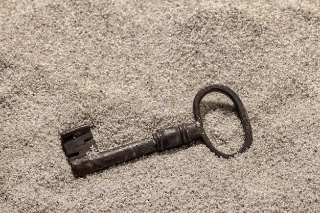 Een oude metalen sleutel op het grove zeezand achtergrond en behang concept kopie ruimte