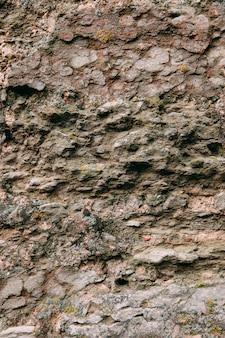 Een oude middeleeuwse stenen muur, gras en mos op. wallpaper, natuurlijke achtergrond, kopieer ruimte, soft focus.