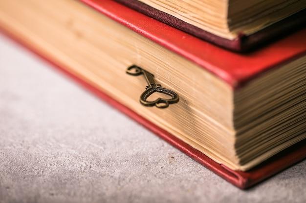 Een oude mooie hartsleutel met legt tussen de pagina's van een oud boek.