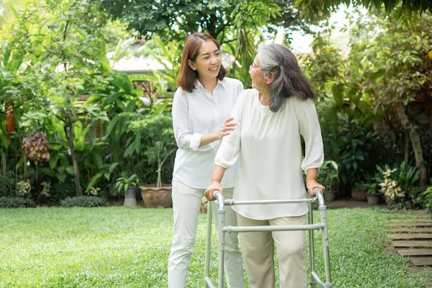Een oude oudere aziatische vrouw gebruikt een rollator en loopt met haar dochter in de achtertuin