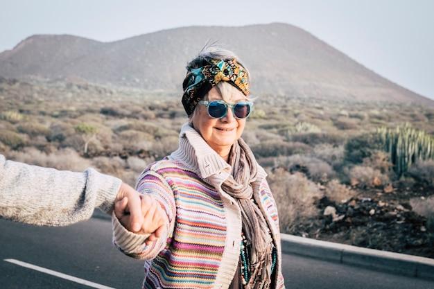 Een oude, oudere, vrolijke vrouw met gekleurde trendy kleding loopt in de buitenlucht, hand in hand met de man